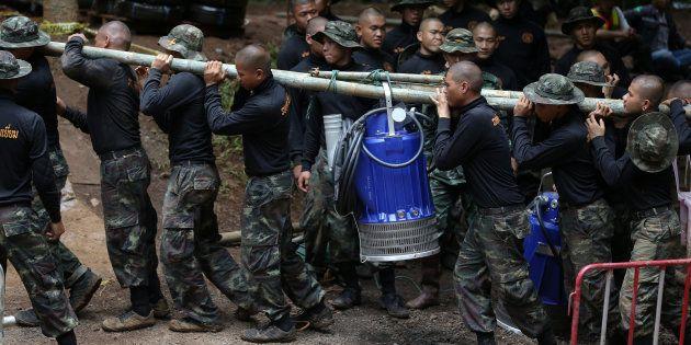 水をくみ出す電動ポンプを運ぶタイの軍関係者ら=7月6日、タイ北部チェンライ
