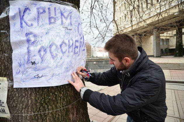 「クリミアよ、ロシアとともに」と書かれた旗に賛同の署名をする男性=2014年3月、シンフェローポリ