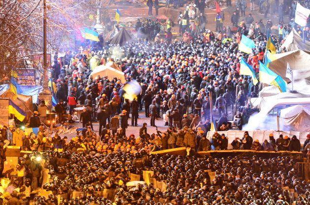 ヤヌコビッチ政権に反対する集会参加者(奥)と衝突する警察隊(手前)=2013年12月、キエフ