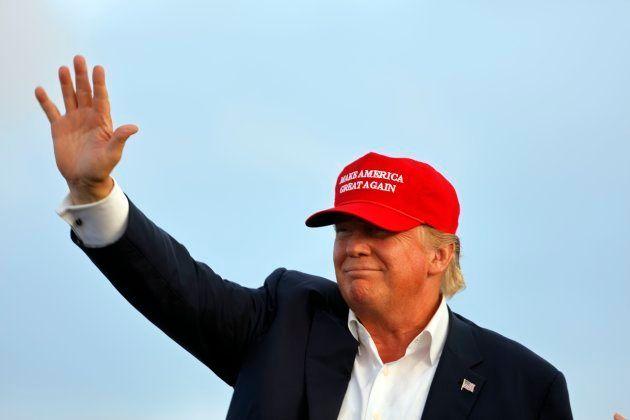 MAGA帽子をかぶって観客に手を振るトランプ大統領