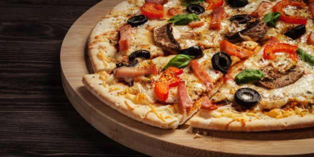 Letterbox panorama of sliced ham pizza with capsicum and olives on wooden board on