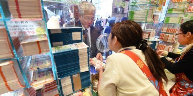 A customer purchases tickets for the 700 million yen (6 million USD) 'Year-end Jumbo Lottery' as the...
