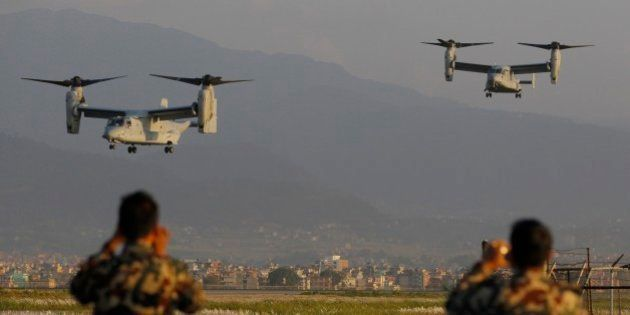 Nepalese soldiers take pictures as US Air Force Bell Boeing V-22 Osprey aircrafts arrive at the Tribhuvan...