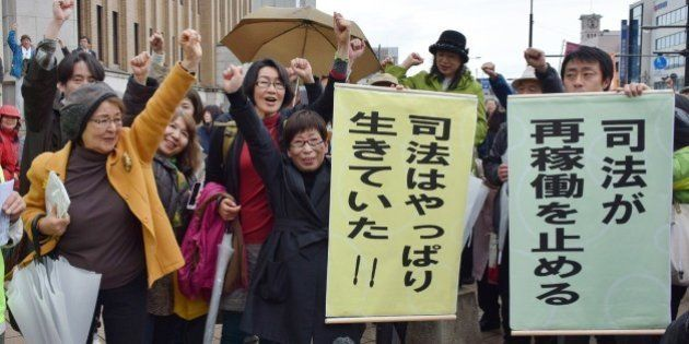 Anti nuclear activists raise their fists in the air to celebrate as the Fukui district court issued a...