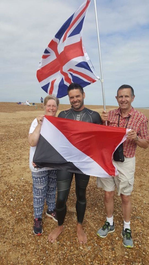 遠泳を成功させてシーランド公国の国旗を掲げるリチャード・ロイヤルさん(中央)