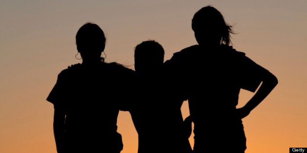 A silhouette of three children bonding at sunset. Affection. Love. Relationships.