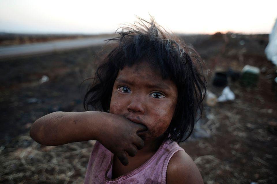 ブラジルのマトグロッソ・ド・スル州に暮らす先住民グラアニ=カイオワ族の少女サンドリーリーさんが、正体不明の放火犯によって全焼した小屋の前に立つ。グラアニ=カイオワ族は、先祖から伝わる土地の所有権をめぐって流血する衝突に巻き込まれている