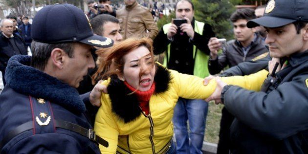 Azerbaijan's policemen detain an opposition activist during a rally against the devaluation of the national...