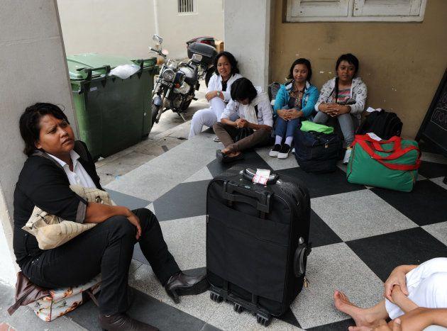 シンガポールに到着し、家政婦としての登録を待つインドネシアの出稼ぎ労働者たち=2012年