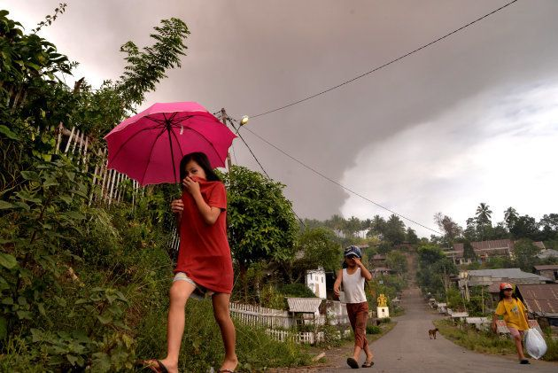 ソプタン山の噴火で灰が降る中、歩く住民ら=10月3日、スラウェシ島