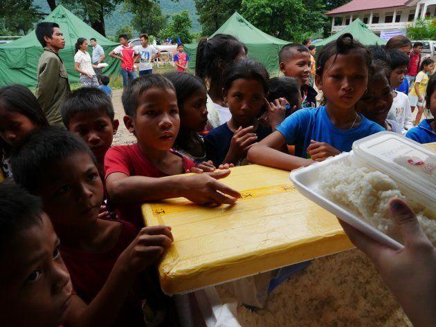ラオス南東部アッタプー県から車で約3時間離れた場所につくられた臨時避難所では、倉庫のような場所に避難した人たちが身を寄せていた=2018年7月、染田屋竜太撮影