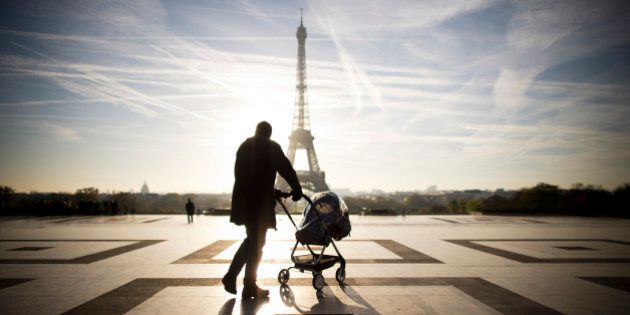 A person walks with baby-buggy in front of the Eiffel tower on November 11, 2013 at the Trocadero in...