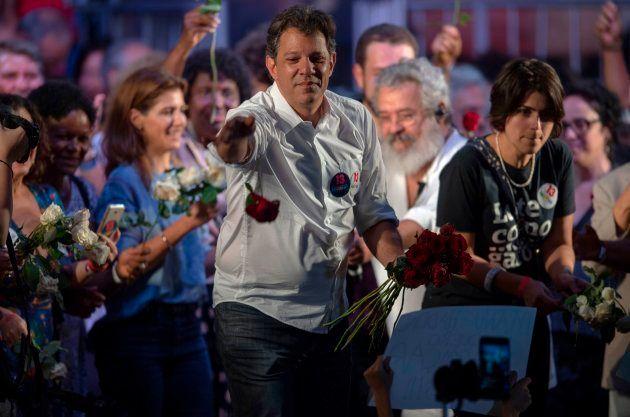 集会で支持者に花を配るフェルナンド・アダジ氏=10月23日、リオデジャネイロ