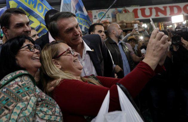 支持者たちとスマートフォンで写真を撮るボルソナーロ氏(左から4人目)=8月27日、リオデジャネイロ