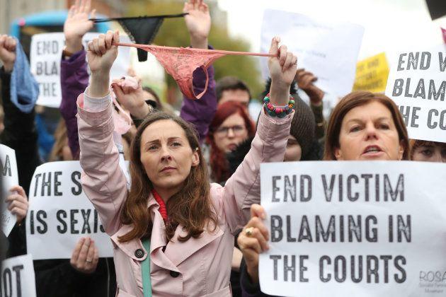 被害者をサポートするためにダブリンに集まった人たち。ソングを頭上に掲げ「裁判所での被害者非難をやめて」と訴える