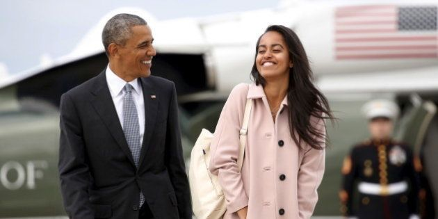U.S. President Barack Obama and his daughter Malia walk from Marine One to board Air Force One upon their...
