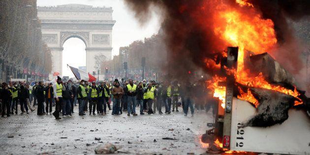パリ・シャンゼリゼ通りでトラックを燃やすデモ隊