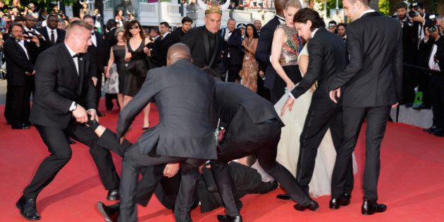 CANNES, FRANCE - MAY 16: A man invades the Red Carpet and is held by security at the 'How To Train Your...