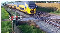 間一髪!踏切を渡る自転車に猛スピードの列車が大接近。紙一重で命拾いする(動画)