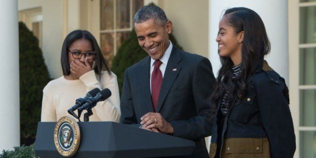 US President Barack Obama laughs with daughters Malia (R) and Sasha before 'pardoning' the National Thanksgiving Turkey in the Rose Garden at the White House in Washington, DC, on November 25, 2015. The President pardoned Honest and his alternate Abe, both 18-week old, 40-pound turkeys. The names of the turkeys were chosen from submissions from California school children. After the pardoning, the turkeys will be on display for visitors at their permanent home at Morven Parks Turkey Hill, the historic turkey farm located at the home of former Virginia Governor Westmoreland Davis (1918-1922) in Leesburg, Virginia. AFP PHOTO/NICHOLAS KAMM / AFP / NICHOLAS KAMM (Photo credit should read NICHOLAS KAMM/AFP/Getty Images)
