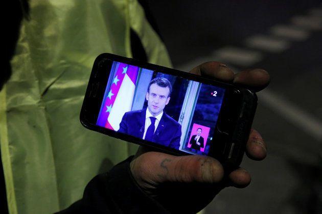 マクロン大統領の演説動画をスマホで視聴する「黄色ベスト」の人たち
