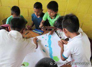 「暴力のない村」をテーマに絵を描く男の子たち