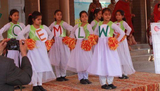 白いドレスに、色鮮やかな「WELCOME」の文字をつけたり、玉房を手にして踊る子どもたち