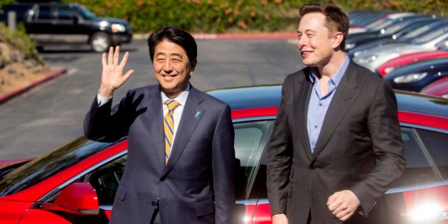 Japanese Prime Minister Shinzo Abe stands with Tesla CEO Elon Musk after returning from a brief test...
