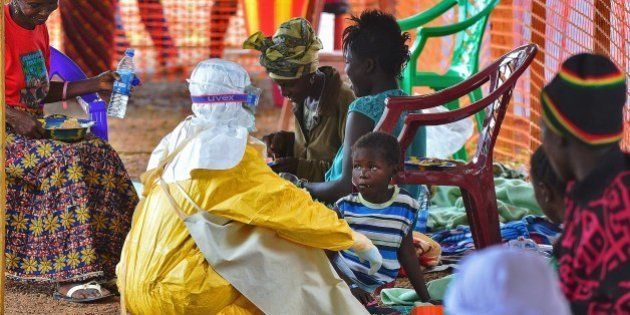 An MSF medical worker feeds an Ebola child victim at an MSF facility in Kailahun, on August 15, 2014....
