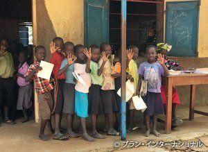 先生にテストの採点をしてもらうために列をつくる子どもたち