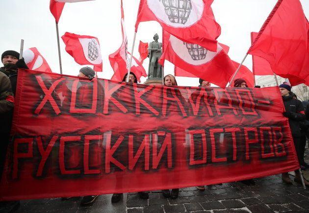 「北海道はロシアの島だ」と書かれた横断幕を掲げる人たち=1月20日、モスクワ