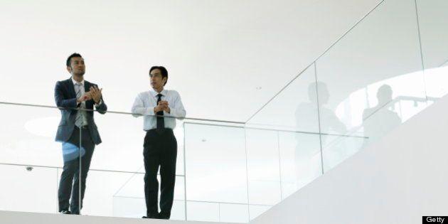 Businessman and mature businessman talking in office hallway resting arm on glass wall.Yokosuka Museum...