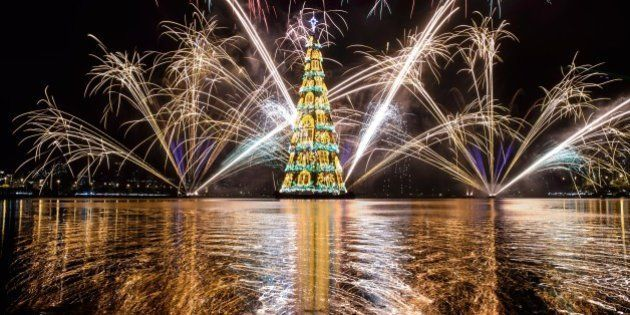 View of fireworks during the inauguration of an 85-meter-high floating Christmas tree at Rodrigo de Freitas lagoon in Rio de Janeiro, Brazil, on November 29, 2014. The world highest floating Christmas tree registered by the Guinness World Records was inaugurated for its 19th time Saturday night and will be illuminated by 3.1 million lights every night until the end of the year. AFP PHOTO / YASUYOSHI CHIBA        (Photo credit should read YASUYOSHI CHIBA/AFP/Getty Images)