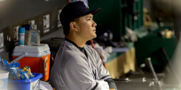 CLEVELAND, OH - JULY 8: Starting pitcher Masahiro Tanaka #19 of the New York Yankees sits in the dugout...