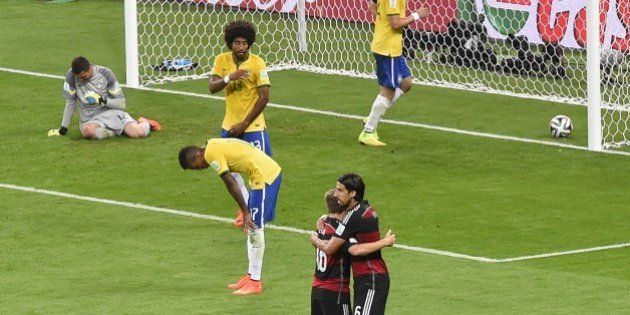 Brazil's goalkeeper Julio Cesar (L) reacts after failing to stop Germany's forward Andre Schuerrle scoring...