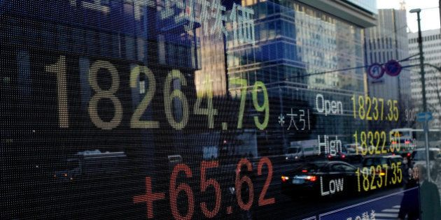 A pedestrian is reflected in an electronic stock board displaying the closing figure of the Nikkei 225...