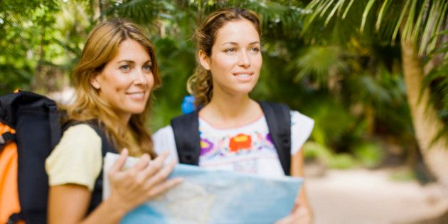 Women backpacking with map