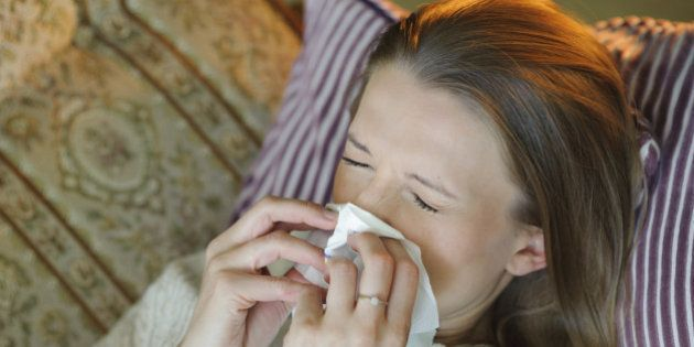 Cold flu illness of woman - tissue blowing runny nose at