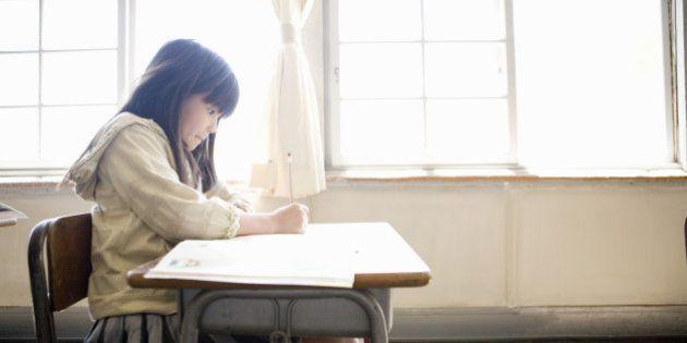 Girl (8-9) writing in school