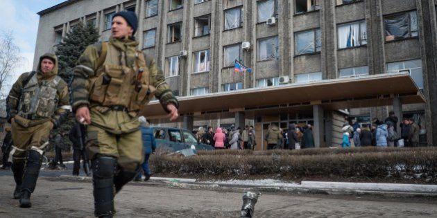 Local residents gather outside a building in the eastern Ukrainian city of Debaltseve on February 20,...