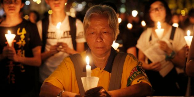 Tens of thousands of people attend a candlelight vigil at Victoria Park in Hong Kong, Saturday, June...