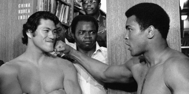 Antonio Inoki smilingly takes it on the chin as Muhammad Ali show newsmen what he will be aiming for...