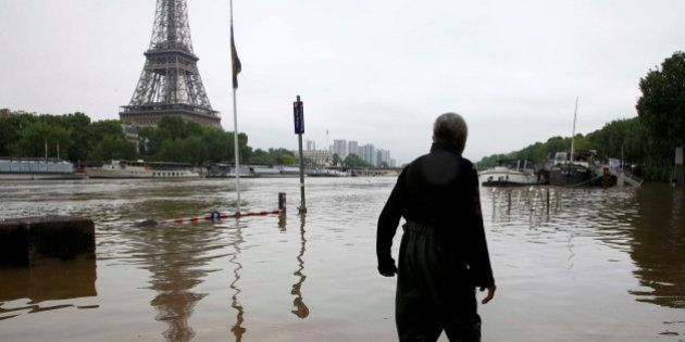 A man walks on a flooded road near his houseboat moored near the Eiffel towel during flooding on the...