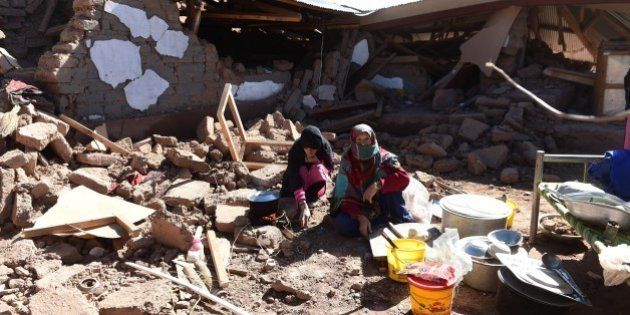 Pakistani earthquake survivors eat in their destroyed home in Charun Avir village, some 65 km north of...