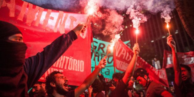 SAO PAULO, BRAZIL - MAY 15, 2014: Black Bloc protesters Group clash with policemen during a protest against...