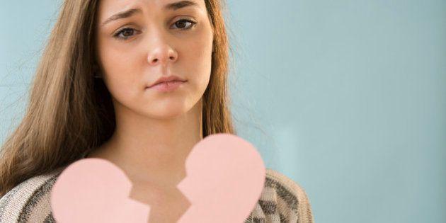 Hispanic girl holding broken heart