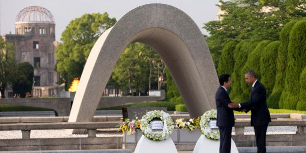 U.S. President Barack Obama, right, and Japanese Prime Minister Shinzo Abe shake hands during a wreath...