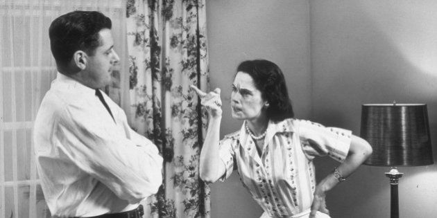 circa 1955: A woman gestures with her index finger as she scolds her husband, who stands with his arms...