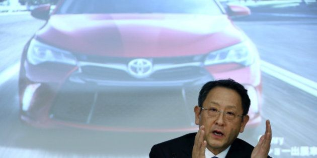 Akio Toyoda, president of Toyota Motor Corp., gestures as he speaks in front of a screen displaying an...