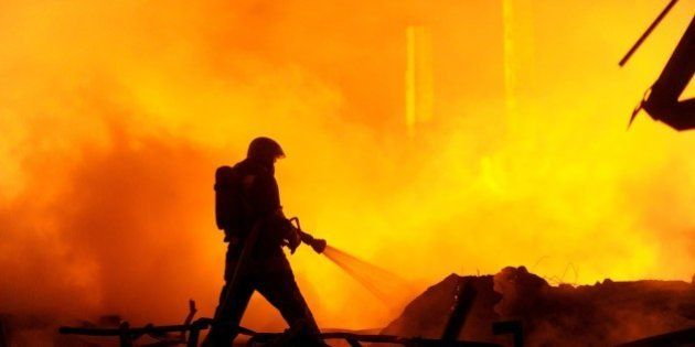 A firefighter works to extinguish a fire at a warehouse of car spare parts in St. Petersburg on October...